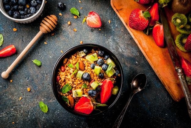 ミューズリーまたはグラノーラとナッツ、新鮮なベリー、フルーツのヘルシーな朝食