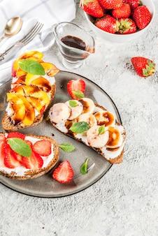 健康的な夏の朝食スナック、フルーツとベリーのライ麦トーストサンドイッチ