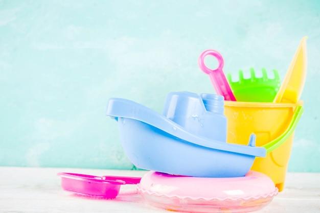 Концепция летних каникул с пластиковой синей лодкой, спасательным кругом и яркими песочными игрушками