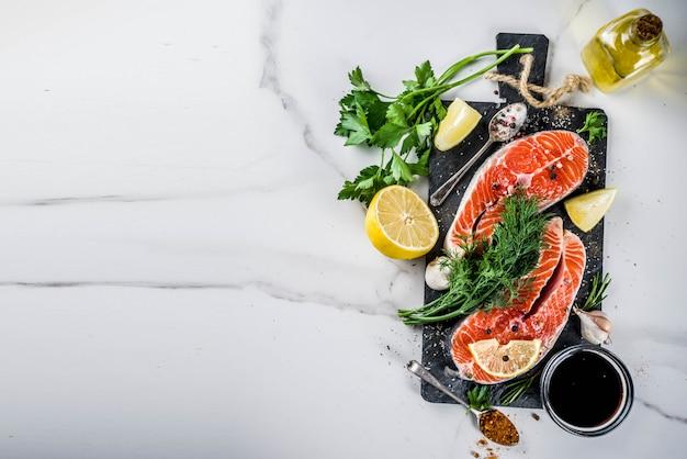Сырые стейки из лососевой рыбы с лимоном, зеленью, оливковым маслом, готовые для гриля, разделочная доска из сланца