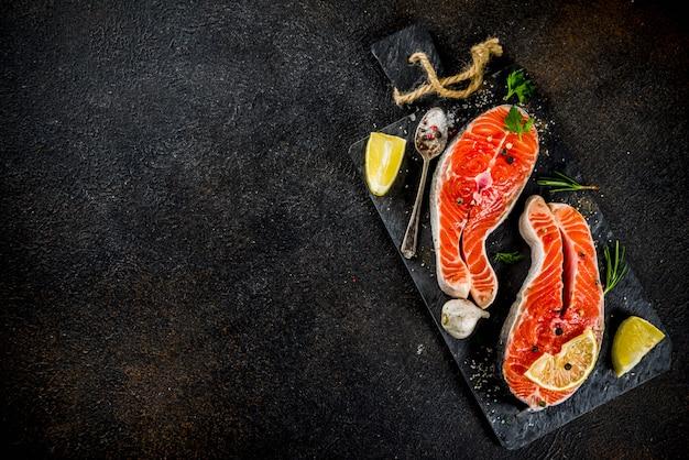 Сырые стейки из лосося с лимоном, зеленью, оливковым маслом, готовые к грилю