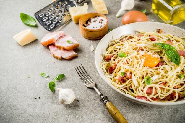 伝統的なイタリアンパスタ、ベーコン入りスパゲッティカルボナーラ、クリーミーなソース、パルメザンチーズ、卵黄、新鮮なバジル