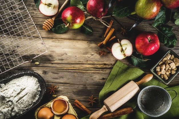 Осенний фон приготовления, концепция выпечки яблочного пирога, свежие красные яблоки, сладкие специи, сахар, мука
