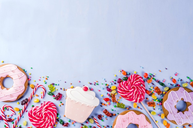 お菓子の創造的なレイアウト、ロリポップ、ゼリー、キャンディ、クッキードーナツ、カップケーキのデザートコンセプト