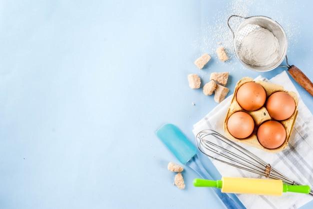 ベーキングエッグ、小麦粉、砂糖、泡立て器、麺棒を調理するための材料と道具