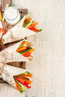 夏のヘルシースナック前菜、メキシコ風のトルティーヤサンドイッチラップ盛り合わせカラフルな新鮮な野菜スティック