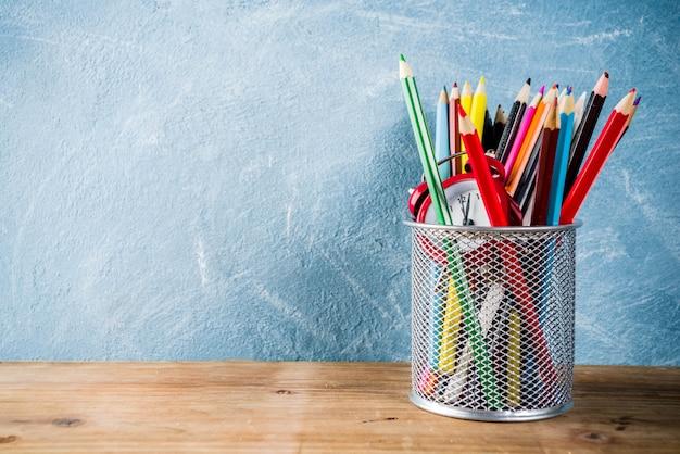 鉛筆と木製の机の上の目覚まし時計で学校概念に戻る