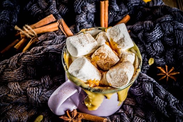 秋、冬の飲み物。クリスマス、感謝祭、ハロウィーンのアイデア。ホットスパイシーカボチャホワイトチョコレート、マシュマロ、シナモン、アニス