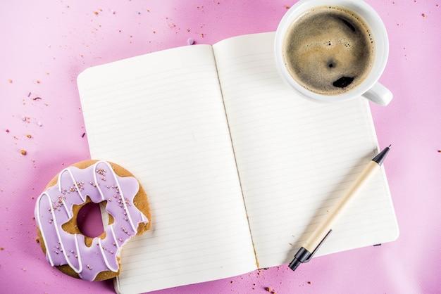コーヒーカップと砂糖のコーティングとメモ帳とビスケットドーナツ