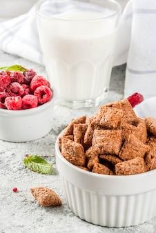 Ингредиенты для здорового завтрака. хлопья для завтрака, стакан молока или йогурта, малина