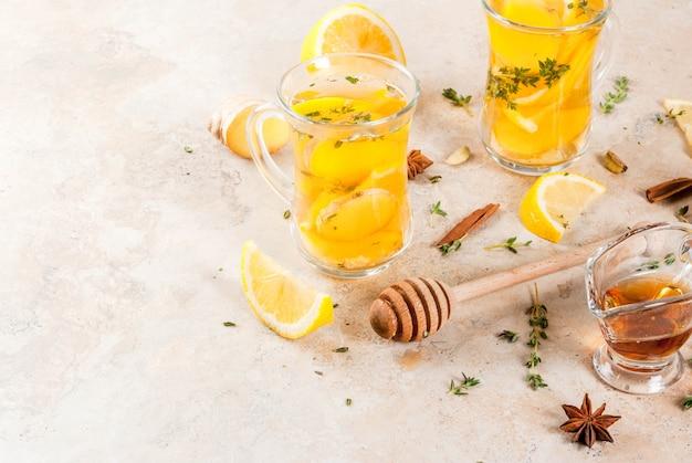 秋と冬の伝統的な飲み物。レモン、ジンジャー、スパイス入りの温かいお茶
