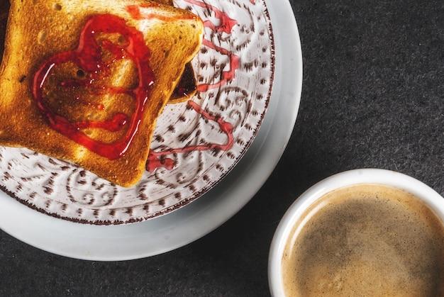 Идея завтрака на день святого валентина с кофейной кружкой, поджаренным хлебом с красным клубничным джемом