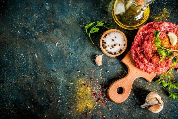 Котлеты из сырого бургера с солью, перцем, маслом, зеленью и специями