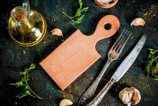 料理のコンセプト、スパイス、ハーブ、カッティングボードと食材を使った夕食を準備するための油