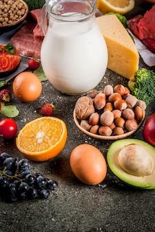 健康的な食事の背景。有機食材、スーパーフード:牛肉と豚肉、鶏肉の切り身、サケの魚、豆、ナッツ、牛乳、卵、果物、野菜