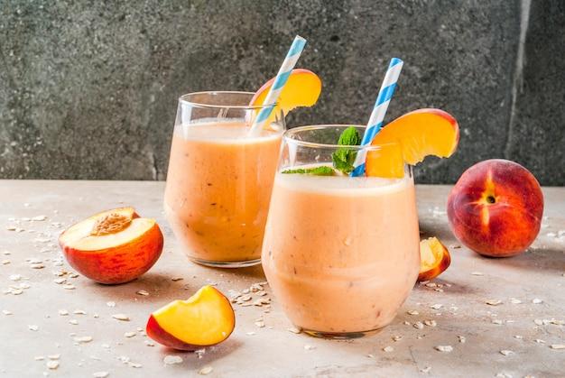 健康的な食事。朝食、スナック。新鮮な桃のスムージーとオートミールを飲む