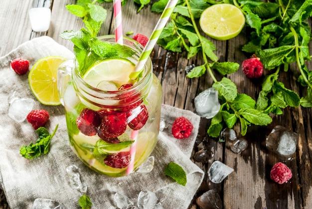 Летние напитки, коктейли. веганская еда. настой детокс воды с лаймом, мятой и свежей органической малиной