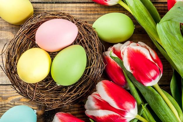 木製の背景にチューリップの花と色とりどりのイースターエッグ