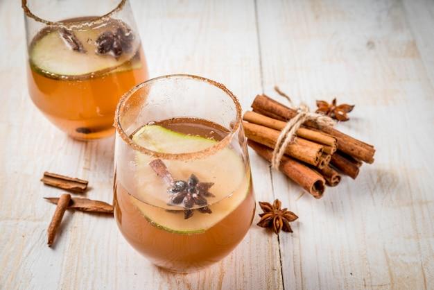 秋の飲み物。グリューワイン。ナシ、サイダー、チョコレートシロップの伝統的な秋のスパイシーなカクテル