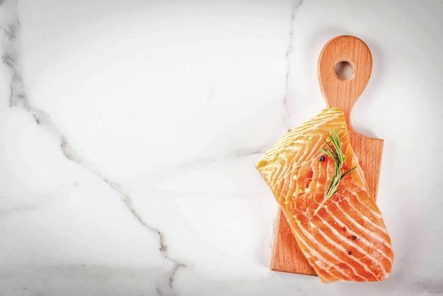 白い大理石の背景に新鮮な生の魚サーモンステーキフィレスパイスライムローズマリー塩
