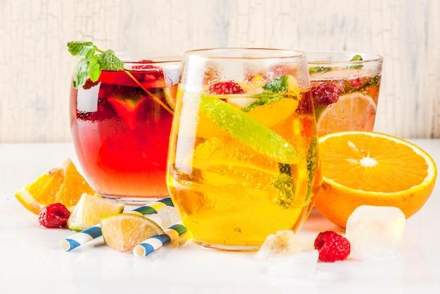 Летний холодный коктейль из трех фруктово-ягодных сангрийских напитков. красный белый розовый с яблоком, лимоном, апельсинами и малиной. светлый фон