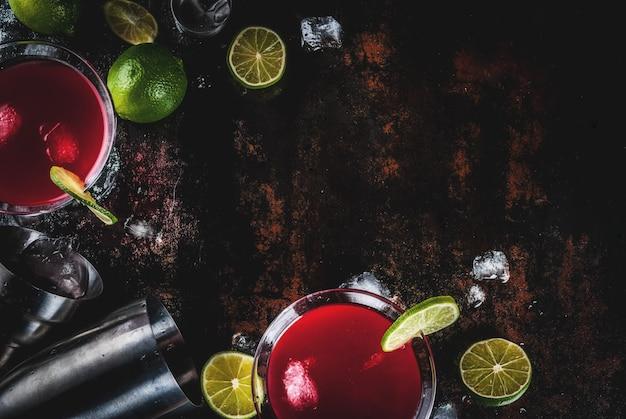 Красный космополитичный коктейль с лаймом в бокале для мартини на темном ржавом фоне