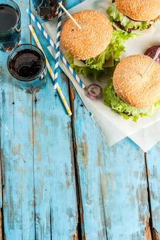 ピクニック、ファーストフード。不健康な食品。ビーフカツレツ、新鮮な野菜、チーズ、甘いソーダ水と古い素朴な青い木製テーブルの上においしい新鮮なおいしいハンバーガー。上面図