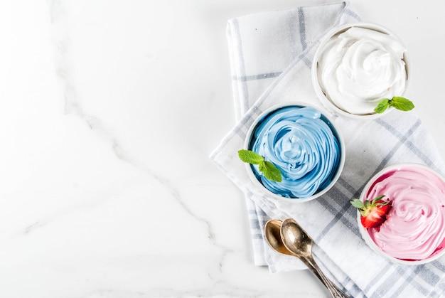 Здоровая диета летний десерт, ванильно-ягодный замороженный йогурт или мягкое мороженое в белых чашах вид сверху