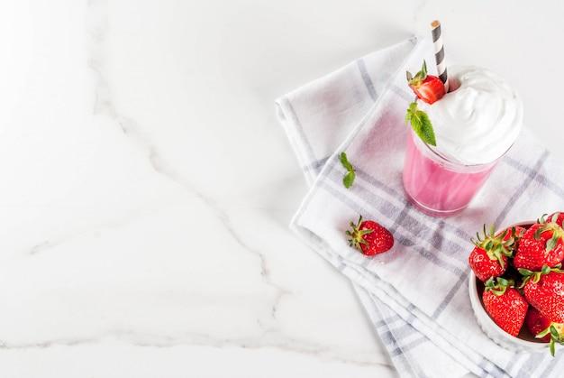 新鮮なベリーと白い大理石の背景にミントの冷たいいちごのミルクセーキトップビュー