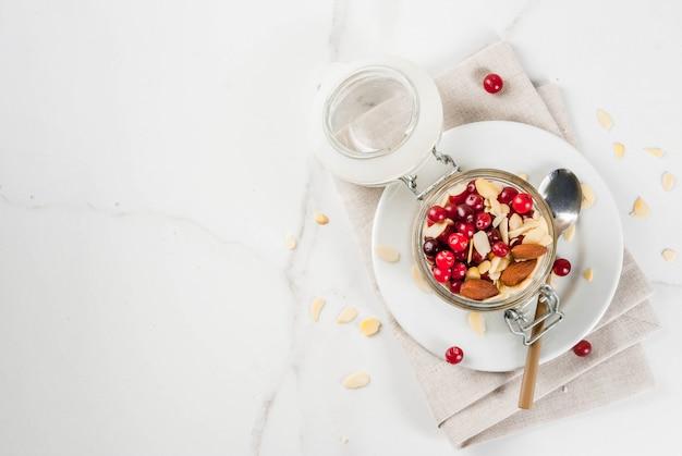 冬の健康的な朝食のレシピ、クリスマスの朝のアイデア。アーモンド、クランベリーを使った一晩のオートミール