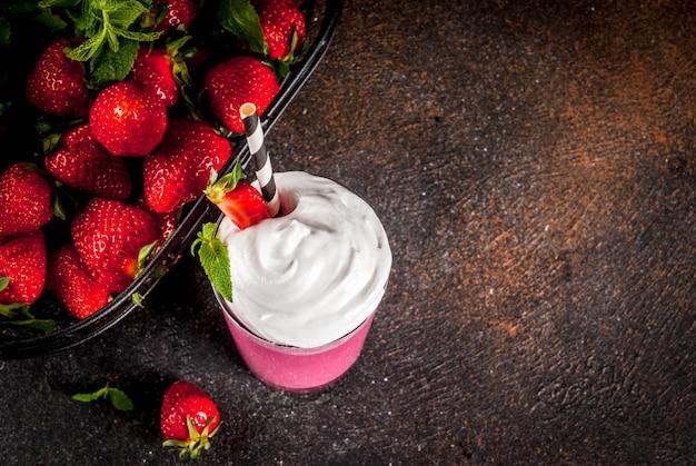 新鮮なベリーと暗い背景の上面にミントと冷たいいちごのミルクセーキ