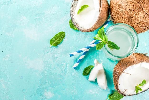 Концепция здорового питания. свежая органическая кокосовая вода с кокосовым кубиками льда и мяты на голубом фоне вид сверху