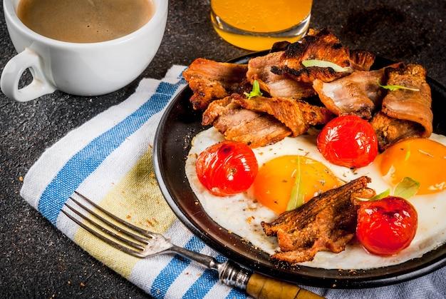 伝統的な自家製イングリッシュアメリカンの朝食、目玉焼き、トースト、ベーコン、コーヒーマグカップとオレンジ