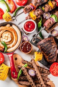 各種バーベキューフードグリル肉、バーベキューパーティーフェスト-シシカバブ、ソーセージ、焼き肉の切り身、新鮮な野菜、ソース