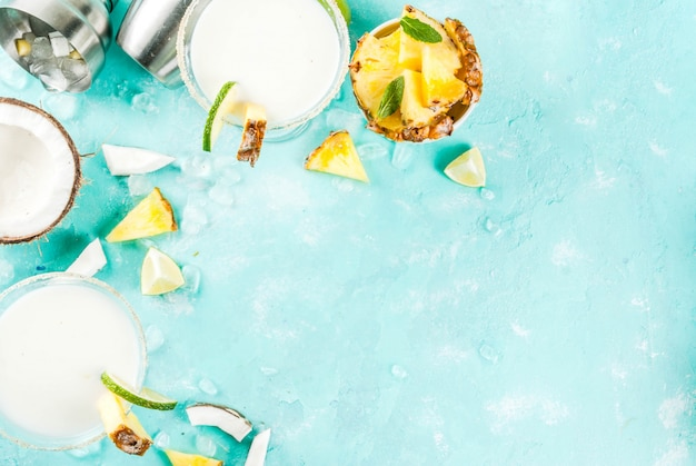 トロピカルドリンク冷凍ココナッツパイナップルマルガリータと冷凍ピナコラーダテキーラパイナップルジュースとライムの明るい青の背景
