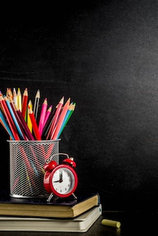 Обратно в школу концепции с книгами будильник цветные карандаши доске фон