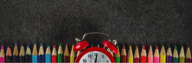 Обратно в школу концепции с книгами будильник цветные карандаши с