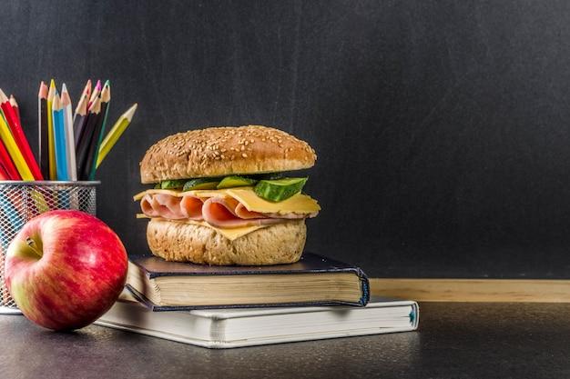 健康的な学校食品のコンセプト、アップル、サンドイッチ、本、黒板背景に目覚まし時計とランチ