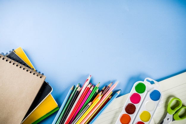 Обратно в школу фон с аксессуарами для школы - краски, карандаши, тетради, книги, ножницы, мел, маркеры, синий фон, над копией пространства