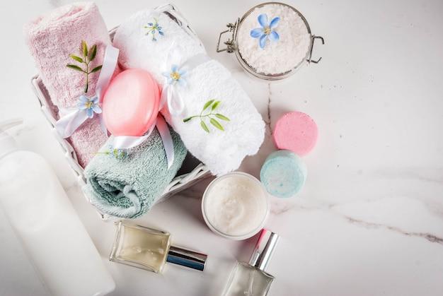 スパリラックスとバスのコンセプト、海の塩、石鹸、バスルームの白い表面に化粧品とタオル、
