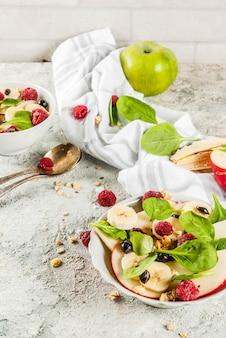 ヘルシーな夏の朝食、フルーツとベリーのサラダ、ほうれん草、グラノーラ、リンゴとバナナ、白い大理石の表面