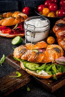 ゴマとケシの実、クリームチーズ、ハム、大根、ルッコラ、チェリートマト、きゅうり、暗いコンクリートの表面に食材を使ったさまざまな自家製ベーグルサンドイッチ