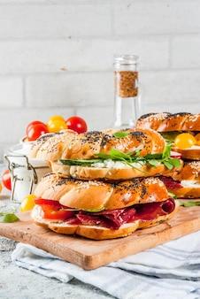 ゴマとケシの実、クリームチーズ、ハム、大根、ルッコラ、チェリートマト、きゅうり、白灰色のテクスチャーサーフェスを備えたさまざまな自家製ベーグルサンドイッチ