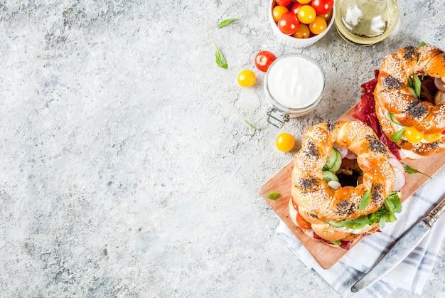 ゴマとケシの実、クリームチーズ、ハム、大根、ルッコラ、チェリートマト、きゅうり、ホワイトグレーテクスチャ表面トップと様々な自家製ベーグルサンドイッチ