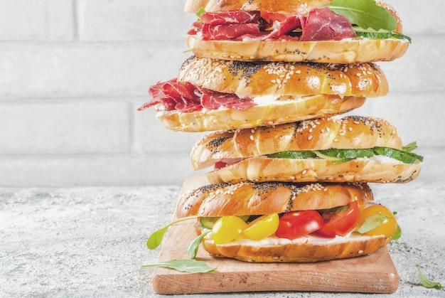 ごまとケシの実、クリームチーズ、ハム、大根、ルッコラ、チェリートマト、きゅうり、白灰色のテクスチャーサーフェスと様々な自家製ベーグルサンドイッチのスタック