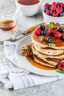 健康的な夏の朝食、新鮮なベリーと蜂蜜と自家製の古典的なアメリカのパンケーキ、朝の明るい灰色の石の表面