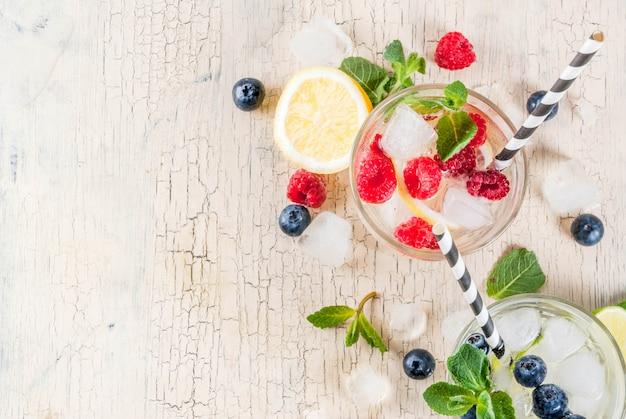 Различные ягодные коктейли с лимонадом или мохито, свежая вода со льдом, лимон, лайм, малина, черника, настоянная вода, летние полезные детокс-напитки, легкая поверхность, вид сверху