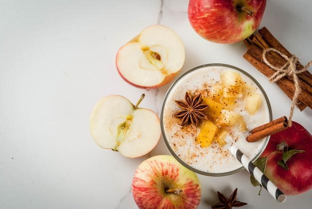 Здоровая веганская еда диетический завтрак или полдник смузи из яблочного пирога с яблоками, йогуртом, корицей, специями, грецкими орехами в стакане на белом мраморном столе