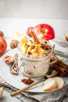 健康的なビーガンフード食事の朝食またはスナックアップルパイ一晩オート麦とリンゴヨーグルトシナモンスパイスクルミ白い大理石のテーブルの上のガラスに
