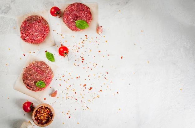 Свежий сырой домашний фарш из говядины со специями и базиликом на белом каменном бетонном столе